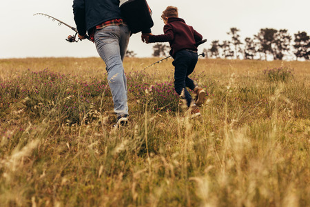 Rear view of a man walking with his kid for fishing holding fishing rods. Cropped shot a person going for fishing with a kid walking on brown grassy field.