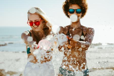 Smiling female friends in bikini splashing water balloon and enjoying at the beach. Cheerful women on a holiday having fun at the seashore.