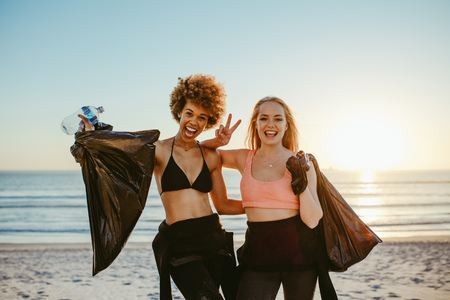 Two female surfers after picking up litter on the beach. Female volunteers after cleaning the beach area, standing together smiling and gesturing victory hand sign.
