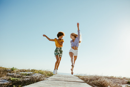Two excited girls running and jumping with joy on boardwalk along the seaside. Two women friends having fun on their vacation.