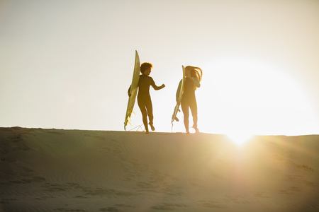 Two female surfers carrying surfboard and running together on the beach. Female surfers against bright sunlight.
