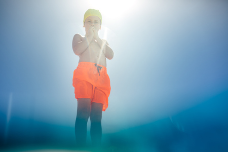 Low angle view of boy in swim trunks standing at the edge of the pool on sunny day. Boy in swimming costume seen from the pool. Reklamní fotografie