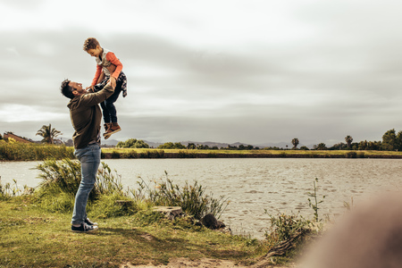 Father and son having fun spending time together outdoors. Man lifting his son high playing with him standing near a lake. Stock Photo