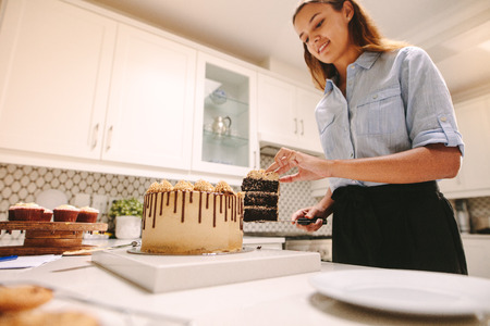 Chef taking a slice from cake to plate with knife. Woman confectioner in kitchen. Zdjęcie Seryjne