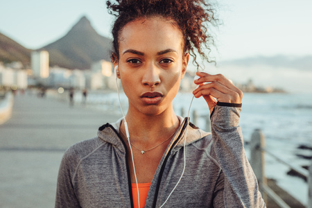 Close up of confident woman runner in sportswear and earphones outdoors. Female taking a break during outdoors workout.