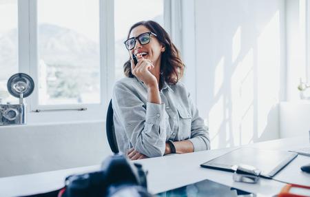 Weiblicher kreativer Fachmann, der an ihrem Schreibtisch wegschaut und lächelt. Fotografin in ihrem Büro.