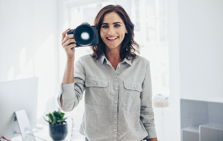 Woman photographer with her professional DSLR camera in office. Woman photographer with digital camera.