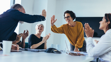 Business people giving each other high five and clapping. Business team celebrating success. Фото со стока