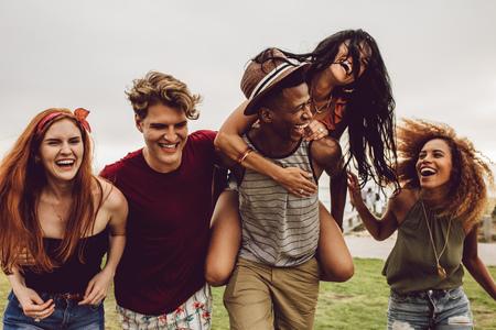 Grupo multirracial de amigos pasando el rato y divirtiéndose al aire libre. Hombres y mujeres jóvenes disfrutando al aire libre en verano.