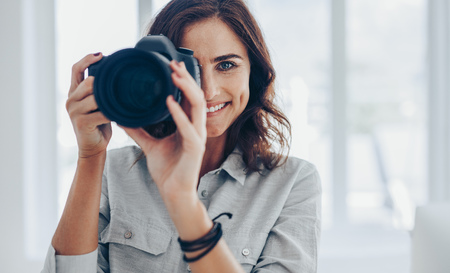 Woman with dslr camera photographing indoors taking few pictures. Happy female photographer taking pictures with professional camera.