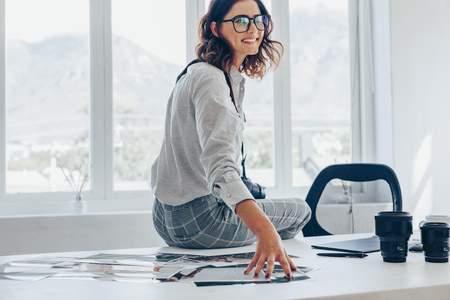 Happy young woman sitting on her and looking at camera. Female photographer with dslr camera at her workdesk, pictures and camera lens on table.