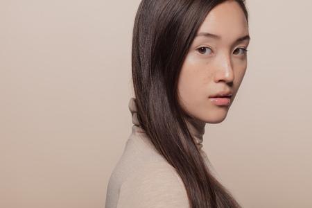 Retrato de mujer con cabello lacio castaño. Mujer asiática con cabello largo mirando a cámara. Foto de archivo