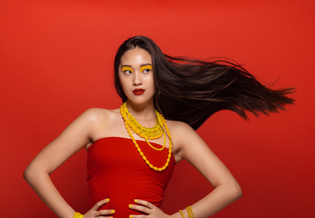 Attractive woman with stylish stage make up and hair flying on red background. Asian female model with creative make up and accessories.