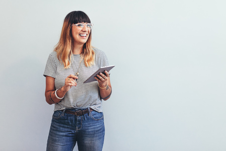 Portrait of a woman standing holding a tablet pc. Smiling woman entrepreneur at office working with a tablet pc.