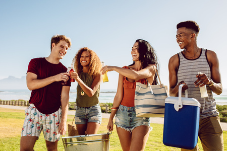 Group of people carrying cooler and beverage tub for party on beach. Diverse group of young people walking outdoors and having drinks.