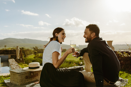 Smiling couple sitting in a wine farm holding glasses of white wine. Couple on a date sitting in a vineyard with a picnic basket by their side. Stok Fotoğraf