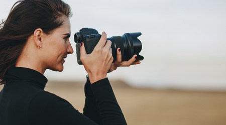 Side view of female photographer shooting with dslr camera outdoors. Woman having a outdoors photo shoot.