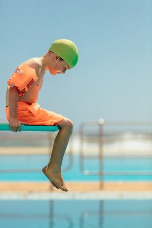 Boy sitting on a diving platform looking down into the swimming pool. Boy in swim gear sitting on spring board. Banque d'images