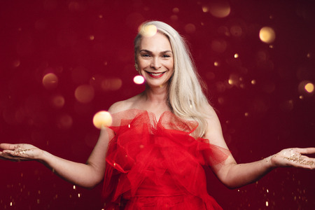 Senior woman throwing golden confetti in air. Pretty mature woman having fun with glitters on red background. 스톡 콘텐츠 - 122865891