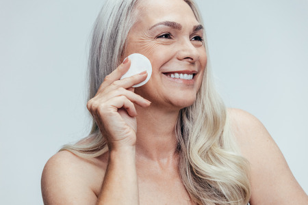 Smiling old woman cleansing her face with a cotton pad against grey background. Happy female cleaning her face skin with a cotton pad.