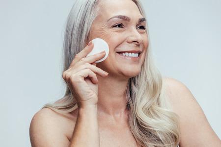 Donna anziana sorridente che si pulisce il viso con un batuffolo di cotone su sfondo grigio. Femmina felice che pulisce la pelle del viso con un batuffolo di cotone.