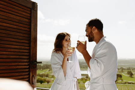 Smiling man and woman holding a glass of wine and talking to each other. Couple in bathrobe standing in balcony of house enjoying a glass of wine.