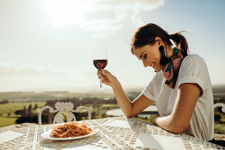 Close up of a woman dining out sitting at a restaurant table. Side view of a smiling woman sitting at the table looking down with a glass of red wine in hand.