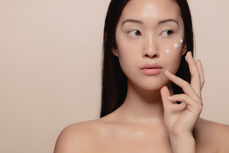 Close up of a beautiful young woman applying moisturizer to her face. Asian female model putting cosmetic cream on her face and looking away.