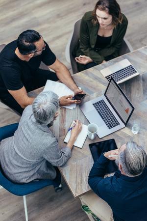 オフィスワーカーはテーブルの周りに集まり、研究を行い、新しいアイデアを実装します。会議で新しい計画について議論するビジネスの人々の高い角度の見方。