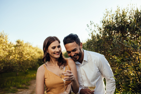 Couple in love walking together holding wine glasses. Couple on a wine date having fun spending time together at a vineyard. Imagens