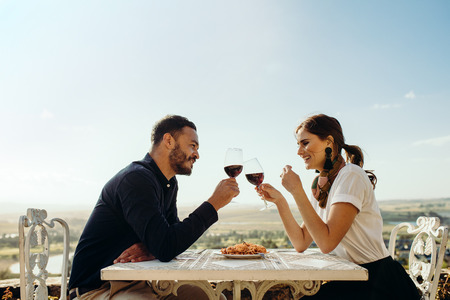 Smiling couple sitting at a restaurant toasting glass of red wine. Happy couple on a date talking to each other holding glass of wine.
