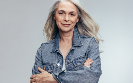 Beautiful senior woman wearing casual denim shirt against grey background. Good looking mature woman standing with her arms crossed and looking at camera. Imagens
