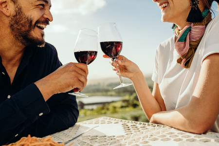 Cropped shot of a happy couple sitting at a restaurant together with a glass of red wine. Close up of a couple on a date talking and spending time with each other toasting glass of wine. Imagens