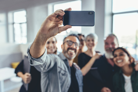 Business people taking selfie of in the office. Business team taking selfie together at startup, with focus on mobile phone.