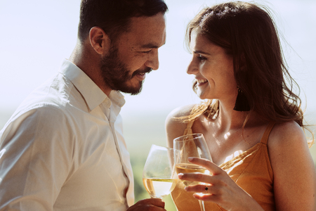 Happy man and woman standing together holding wine and looking at each other. Romantic couple toasting glasses of white wine on a date. Imagens