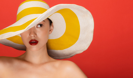Close up portrait of attractive young asian woman wearing summer hat staring at side against red background. Imagens