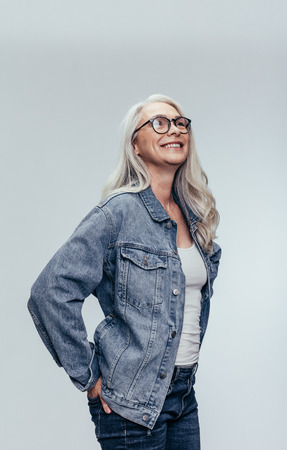 Stylish senior woman in casuals looking at copy space over grey background. Elegant mid adult caucasian woman in denim shirt and eyeglasses looking away.
