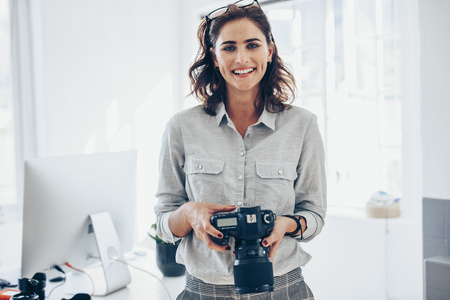 Attractive young woman photographer with her professional camera. Woman photographer with digital camera in office. Imagens