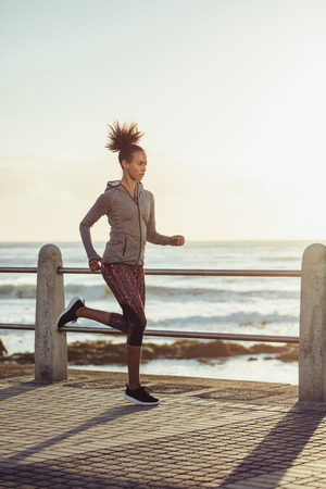 Fit young woman jogging on seaside promenade. Side view of female runner out on a run at sunset.