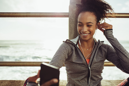 Woman athlete sitting at seaside promenade and listening music from her phone. Runner resting and listening to music during training break.