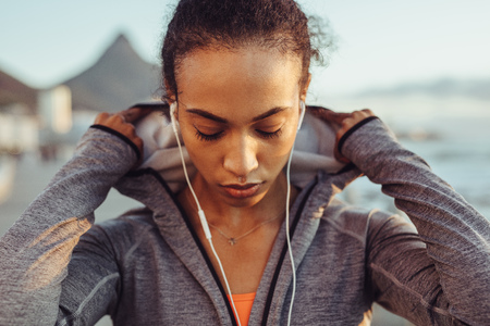 Close up of fitness woman wearing a hooded shirt and earphones outdoors. Female runner on outdoors workout.