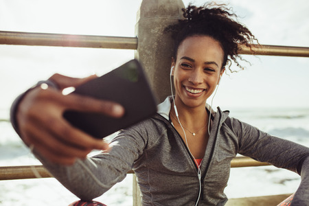 Smiling young woman runner in sportswear taking selfie with her mobile phone. Female relaxing and taking selfie after workout by the sea.