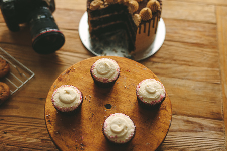 Top view of freshly made cupcake and a cakes on wooden table with a professional camera. Dessert with dslr camera on kitchen counter.