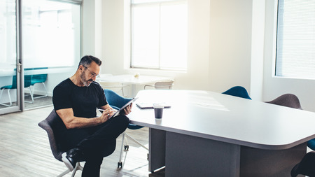 Mid adult businessman working on his digital tablet in a bright office. Entrepreneur with his tablet computer in a modern office space.