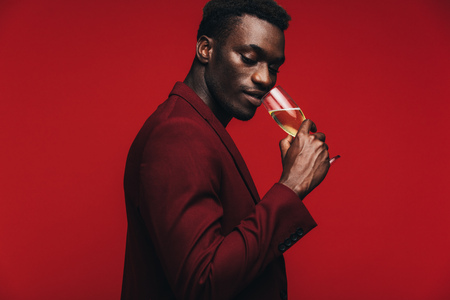 Good looking african guy drinking champagne against red background. Sophisticated african man having a glass if champagne. 写真素材