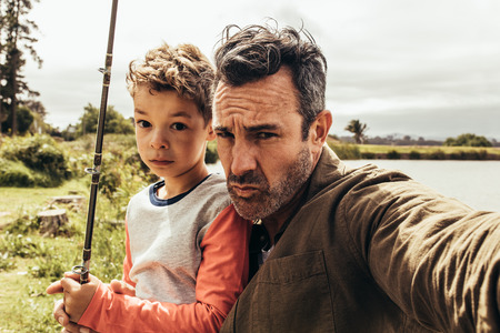 Close up of a man with his son holding a fishing rod standing near a lake. Father and son spending time together fishing near a lake.