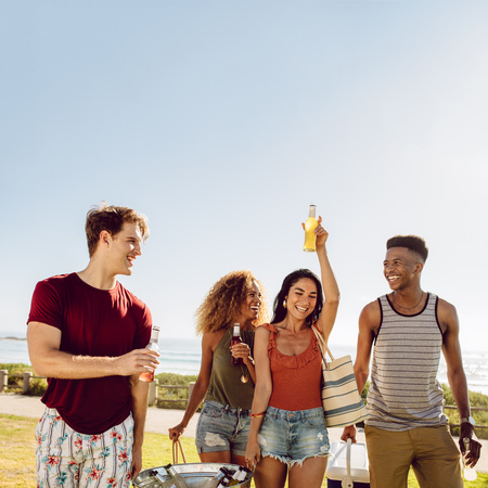 Group of men and women at walking outdoors with beers. Friends having a great time together. Young people going on picnic on a summer day.