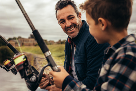 Close up of father and son fishing together sitting near a lake. Smiling man and kid looking at each other enjoying fishing holding fishing rods. Stock Photo