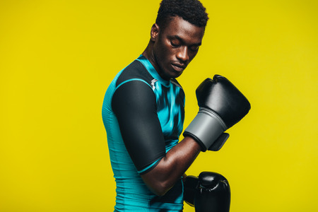 African man with boxing gloves against yellow background. Fit young male boxer practicing. Banco de Imagens