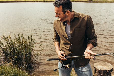 Close up of a man standing on the banks of a lake holding a fishing rod. Man enjoying fishing and having fun singing holding a fishing rod like a guitar.